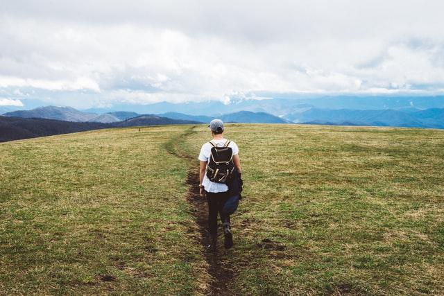 man walking through mountains